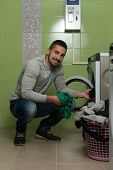 picture of dirty-laundry  - Handsome Young Man In The Laundry Room - JPG