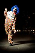 Постер, плакат: Crazy ugly grunge evil clown in town on Halloween making people shock and scared