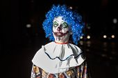 stock photo of ugly  - Crazy ugly grunge evil clown in town on Halloween making people shock and scared - JPG
