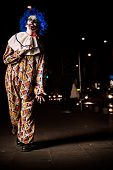 foto of ugly  - Crazy ugly grunge evil clown in town on Halloween making people shock and scared - JPG