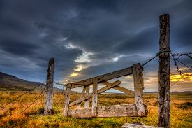 stock photo of iceland farm  - Dilapidated gate on a farm in Iceland with dramatic evening sky in the background - JPG