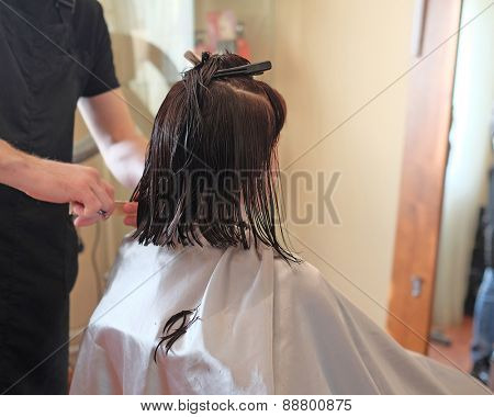Hairdresser making a haircut for a brunette women