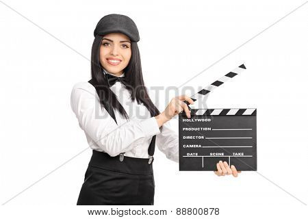 Artistic young female director holding a movie clapper board and looking at the camera isolated on white background