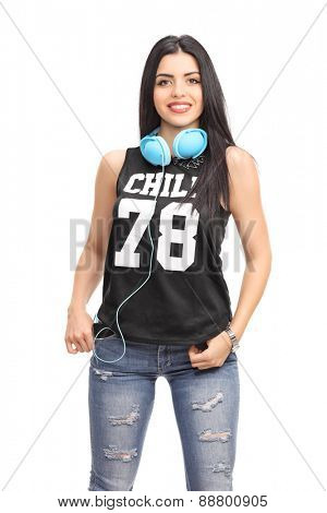 Vertical shot of a beautiful young woman in a hip hop outfit posing with blue headphones around her neck isolated on white background