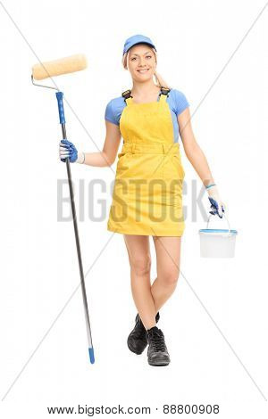 Full length portrait of a young female house painter in a yellow overall walking with a paint roller and a color bucket isolated on white background