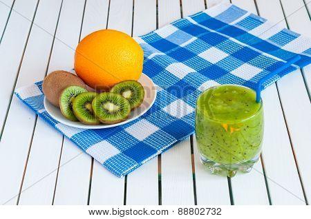 Healthy homemade kiwi juice in glass and fresh orange, kiwifruit on light wooden background.