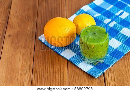 Healthy homemade kiwi juice in glass and fresh orange, kiwifruit on wooden background.