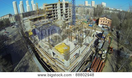 Workers at the construction site of a residential building, aerial view