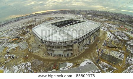 Construction of a football stadium at sunset, aerial view