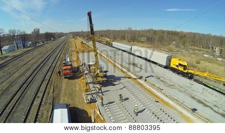 Workers are building the railroad tracks on a sunny spring day, aerial view