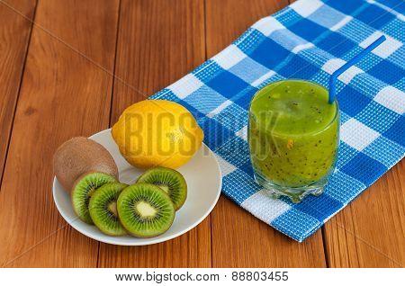 Healthy homemade kiwi juice in glass and fresh lemon, kiwifruit on wooden background.