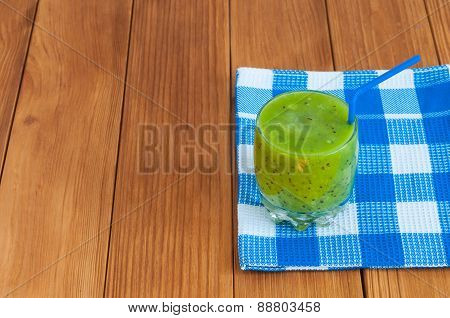 Healthy homemade fresh kiwi juice in glass on wooden background.