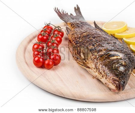 Grilled carp on platter with tomatoes.