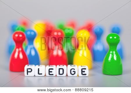 Cube Letters Show Pledge  In Front Of Unsharp Figures
