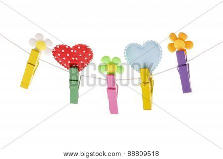 Detail of colorful pegs on rope holding hearts and flowers