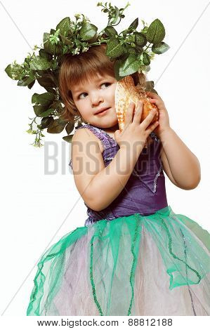 Little Girl In A Beautiful Dress With A Wreath On His Head, And A Seashell In Hands