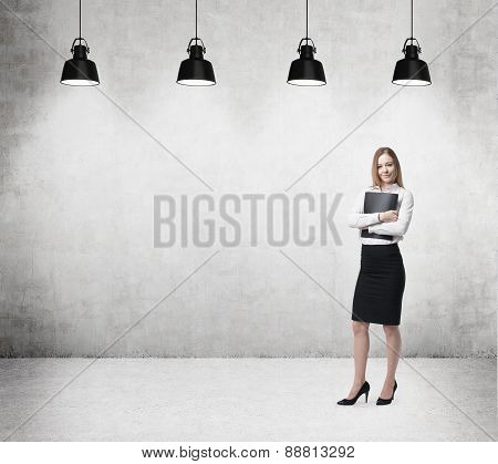 Young Beautiful Business Lady Is Holding A Black Document Case. Businesswoman Is Standing On The Con