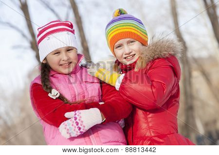 Two cute girls having fun in winter park