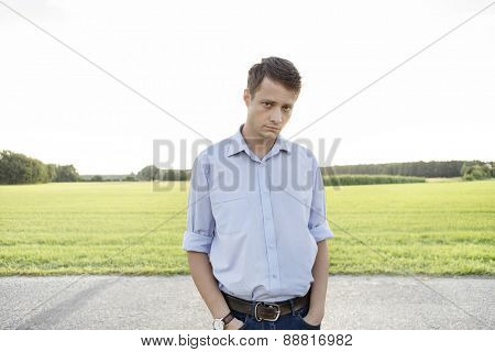 Portrait of sad young man with hands in pockets standing on rural road