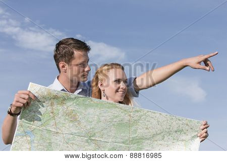 Woman holding map while man pointing away against sky