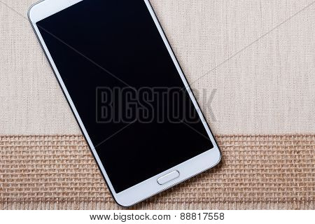 White Modern Smartphone With Blank Screen Lies On Textile.