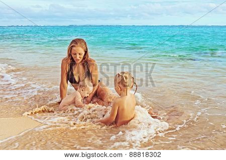 Mother And Her Daughter And Son On The Sea Beach