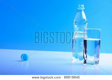 Glass and bottle wit water on blue backgrund