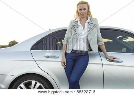 Portrait of beautiful young woman standing by car at countryside
