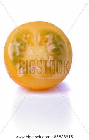 Halved yellow tomato on white background