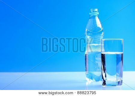 Bottle ang glass of water on blue background