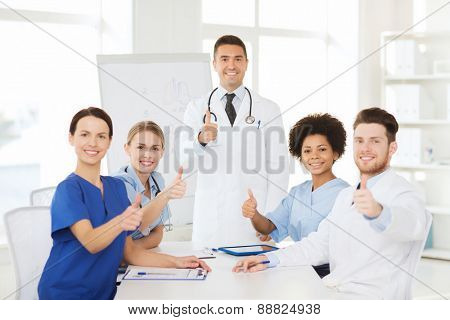 hospital, profession, medical education, people and medicine concept - group of happy doctors meeting on presentation or conference at hospital and showing thumbs up gesture