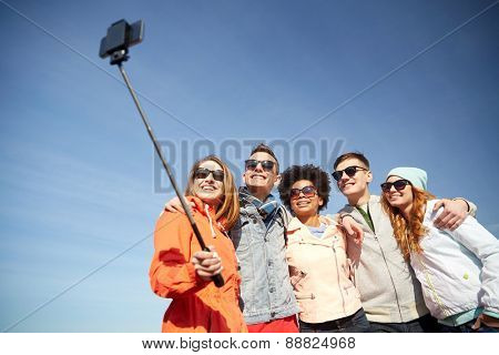 tourism, travel, people, leisure and technology concept - group of smiling teenage friends taking selfie with smartphone and monopod outdoors