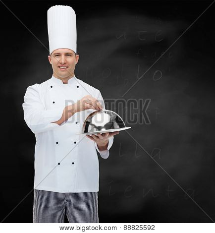 cooking, profession and people concept - happy male chef cook holding cloche over black chalk board background
