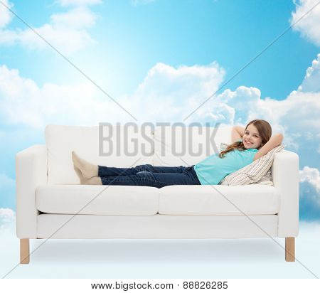 home, leisure, people and happiness concept - smiling little girl lying on sofa over blue sky and white clouds background