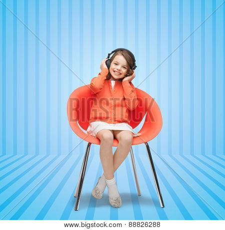 people, leisure, hobby and entertainment concept - happy little girl listening to music in headphones over blue striped background