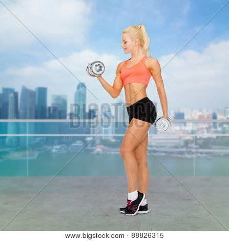 sport, fitness, training, weightlifting and people concept - young sporty woman with dumbbells flexing biceps over city waterside background