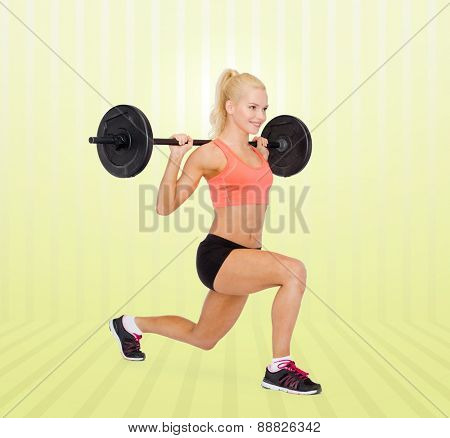 fitness, sport, weightlifting and people concept - sporty woman exercising with barbell over yellow striped background
