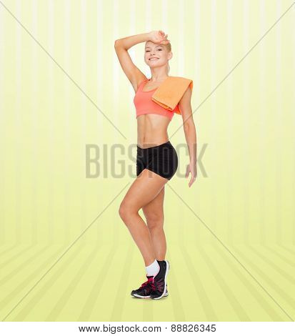 sport, fitness, people and workout concept - smiling sporty woman with towel wiping off sweat over yellow striped background