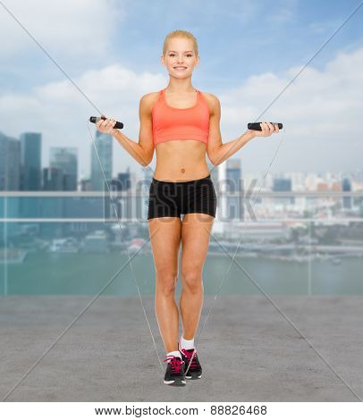 sport, fitness, people and weight loss - smiling sporty woman jumping with skipping rope over city waterside background