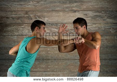 sport, competition, strength and people concept - young men fighting hand-to-hand over wooden wall background