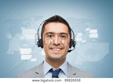 business, people, technology and service concept - smiling businessman in headset over blue background with world map
