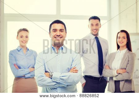 business and office concept - smiling handsome businessman with crossed hands and team in office