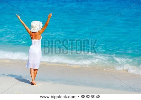 Young woman in a white dress walking on the beach