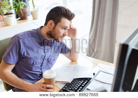 business, startup and people concept - businessman or creative male office worker with computer drinking coffee