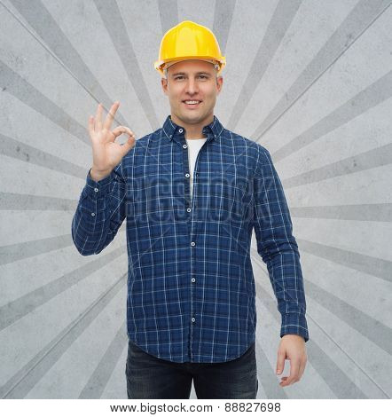 repair, construction, building, people and maintenance concept - smiling male builder or manual worker in helmet showing ok sign over gray burst rays background