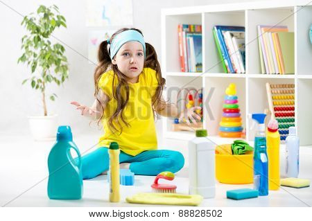 Frustrated kid sitting on floor with cleaning tools