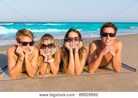 Beach friends together tourits portrait on the sand smiling happy