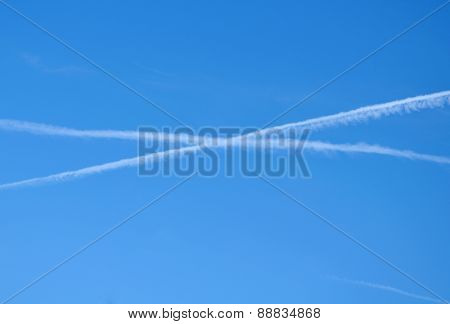 Two Crossed Contrails In Blue Sky