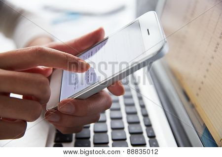 Close Up Of Person At Laptop Using Mobile Phone