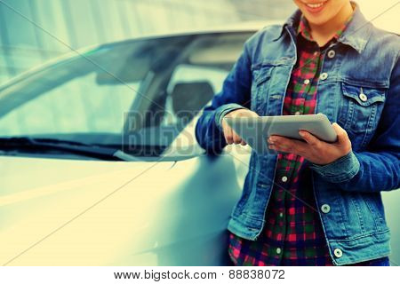 woman use digital tablet leaning on car
